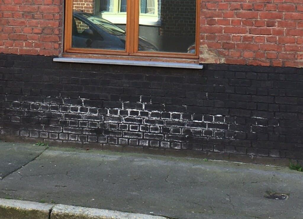 salpetre sur brique peinte en noire